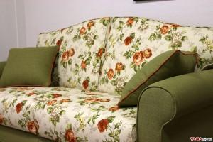 Divano letto classico in tessuto a fiori verde con sfondo panna