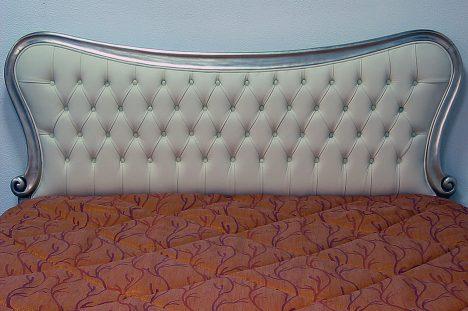 Testata letto con cornice in foglia oro invecchiato in pelle panna bianca e capitonnè