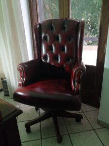 Poltrona da ufficio in pelle rossa anticata in casa del cliente