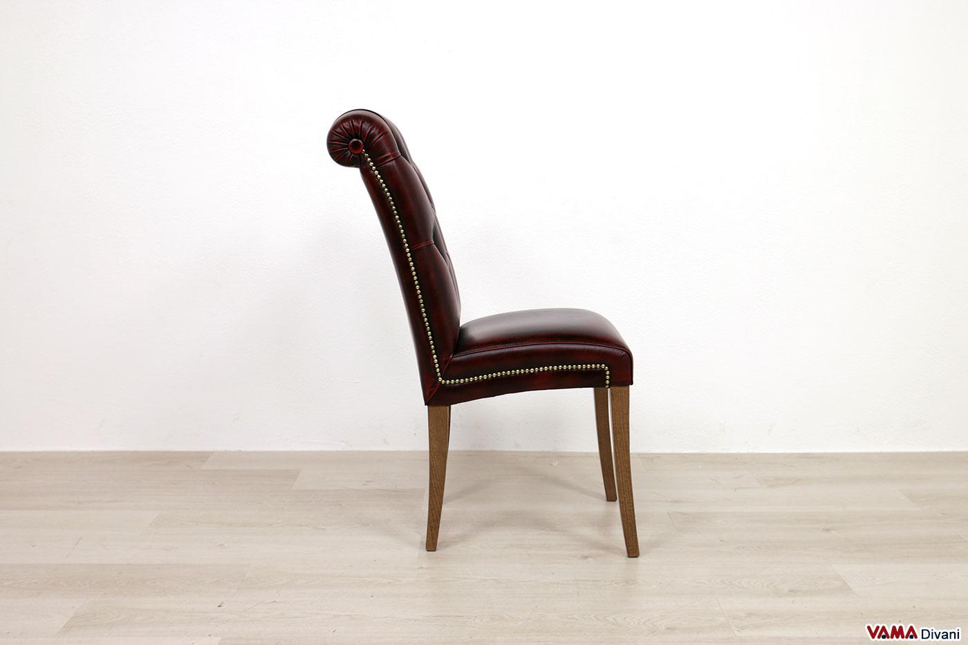Sedia imbottita con gambe alte e finiture in ottone invecchiato
